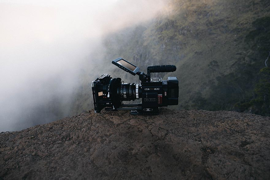 A camera on a rock with mountains in background